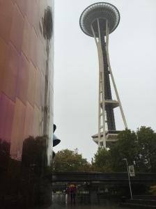 The EMP Museum's glossy surface reflects the Space Needle.
